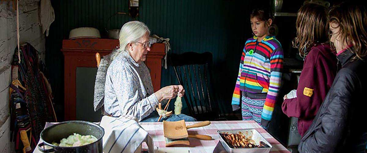 a woman shows antique crafts to girls