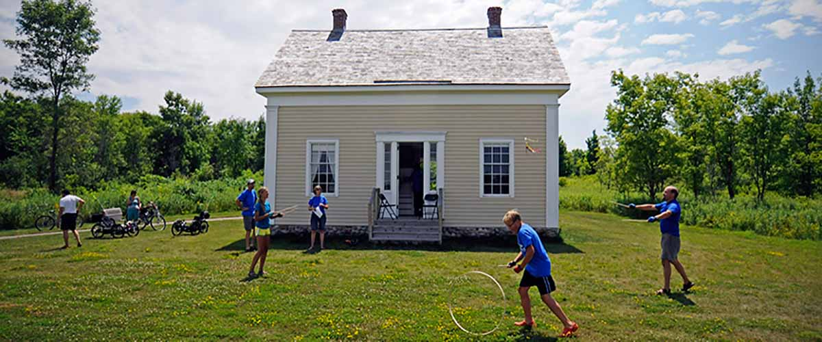 children play in front of an old house