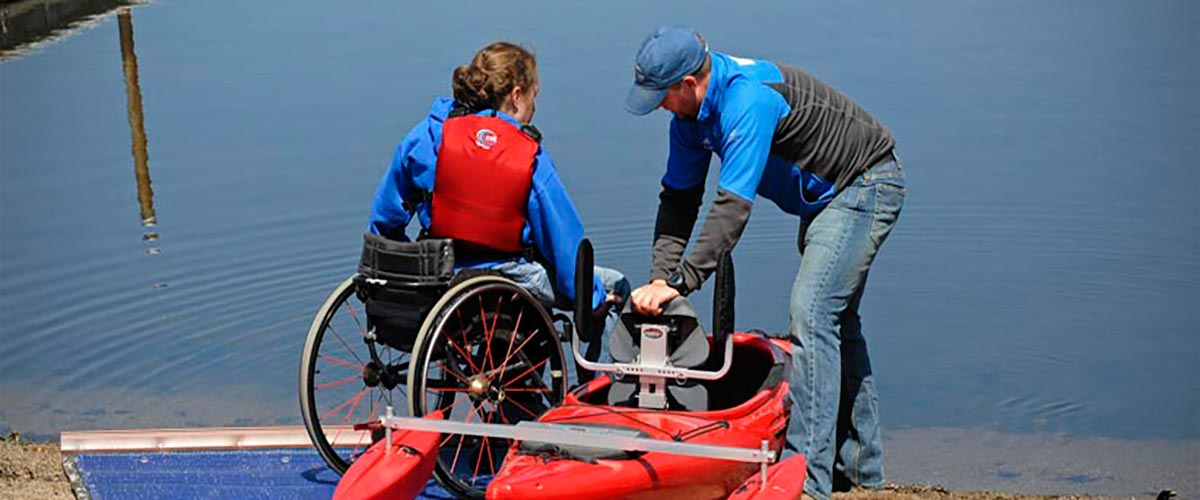 a woman in a wheelchair is helped into a kayak