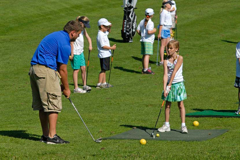 golf instructor teaches young girl