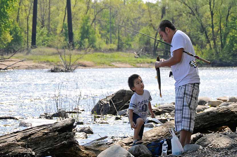 A man and his son fish on the side of a river
