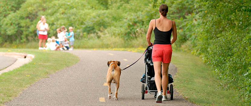 Woman walking her dog on a paved trail
