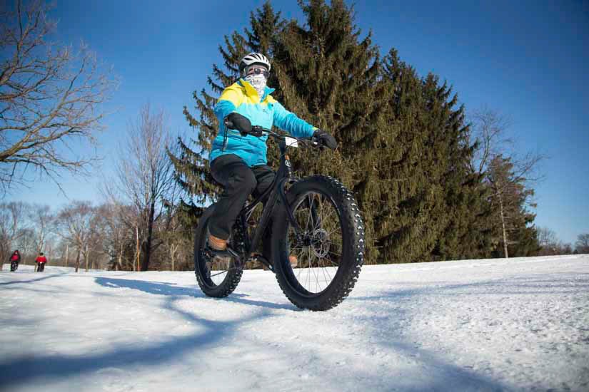 Person riding fat bike on snowy trail