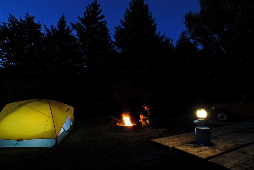 Campfire and tent at night