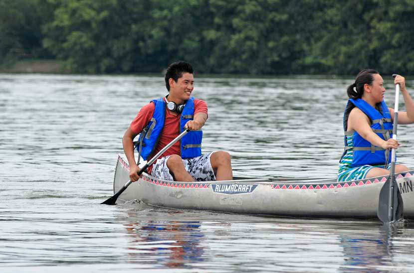 Kids paddle the river in canoes