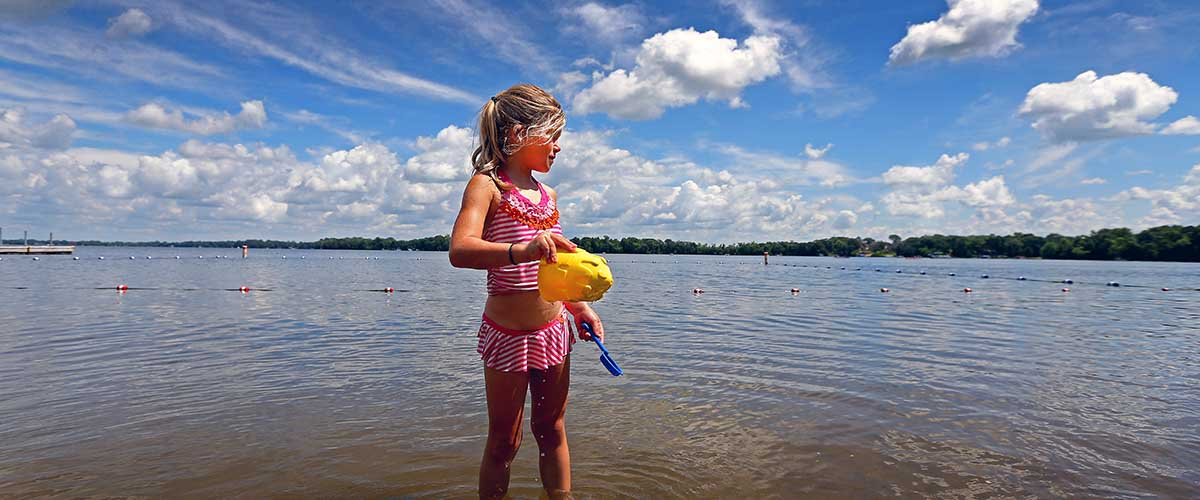 Girl in the lake with sand toys
