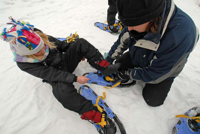 Girl putting on snowshoes