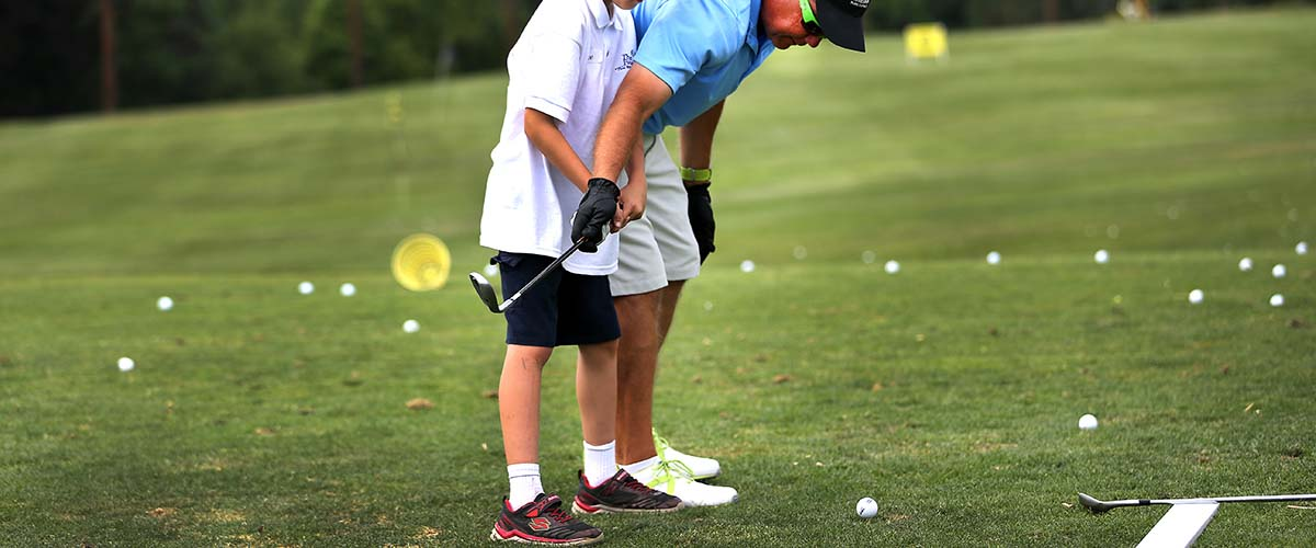 Instructor assist young golfer with swing