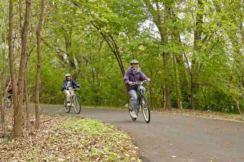 Two bikers on a paved trail