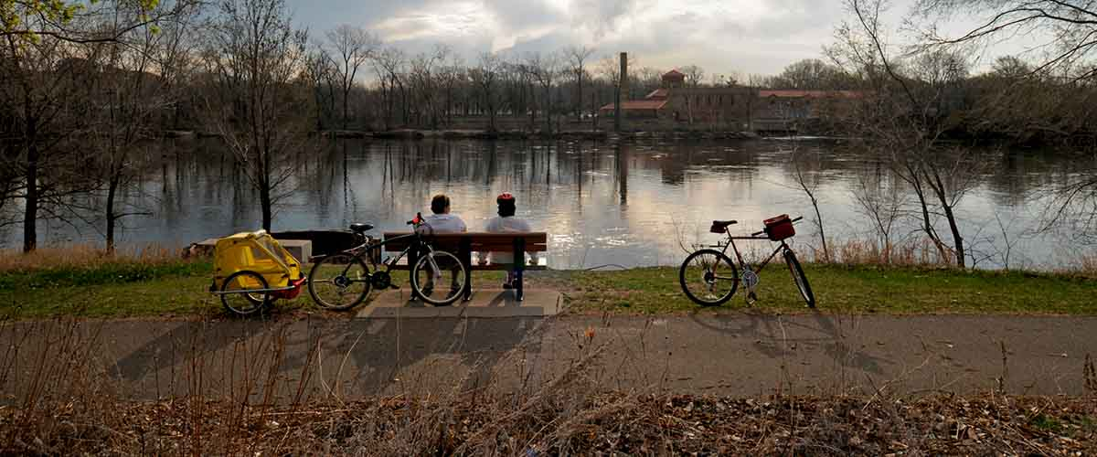 Bikers resting on a bench viewing the river