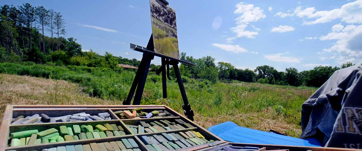 Set of artist pastels with easel on the landscape