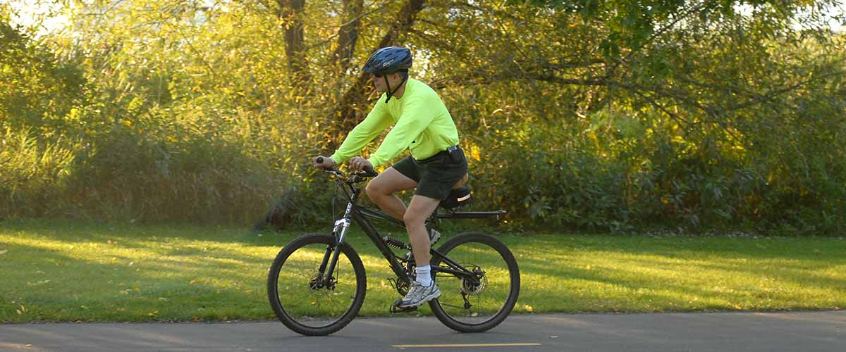 Man biking on paved trail