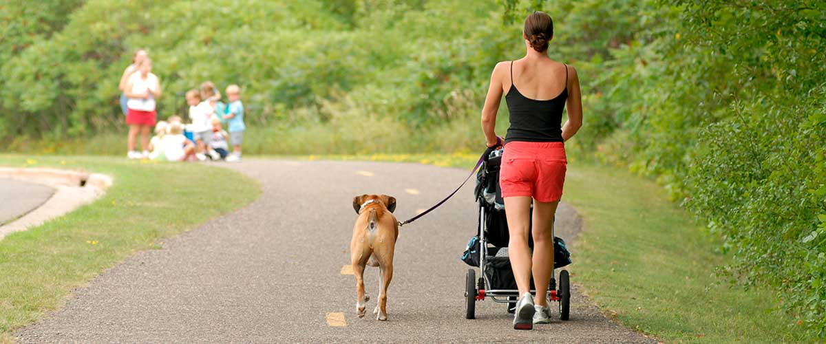 Women walking on paved trail with stroller and dog on leash