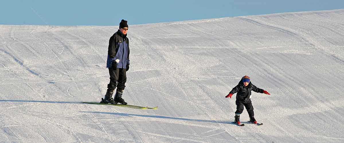 Adult and child on freshly groomed hill