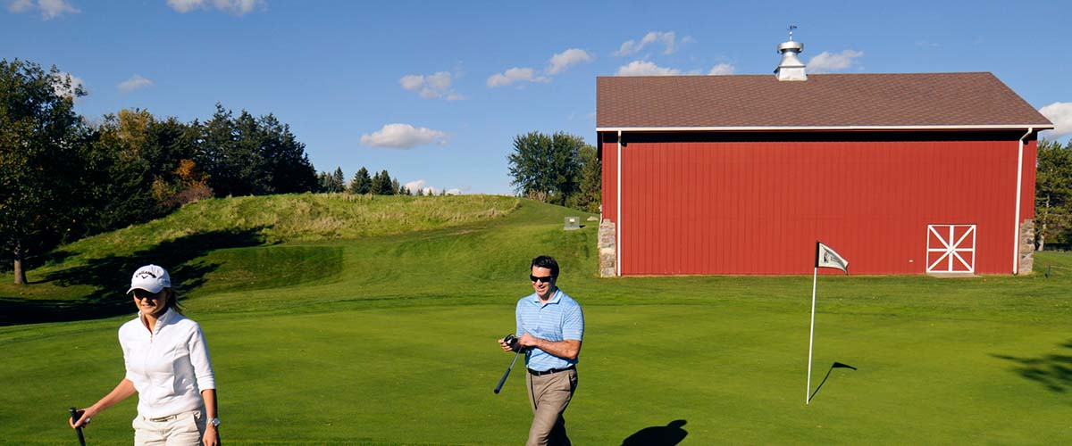 Golfers and the red barn at Baker National