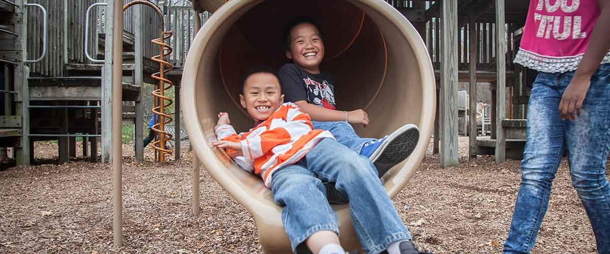 Children coming out of a tube slide