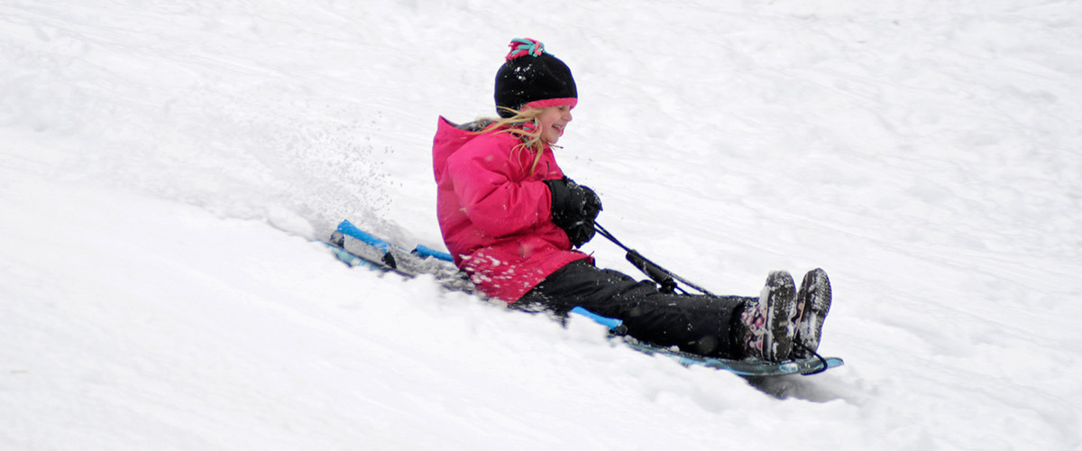 Girl sledding down hill