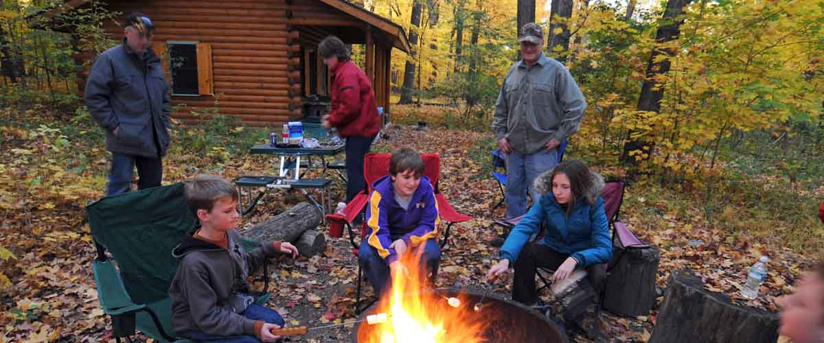 group gathered around a bonfire near a camper cabin