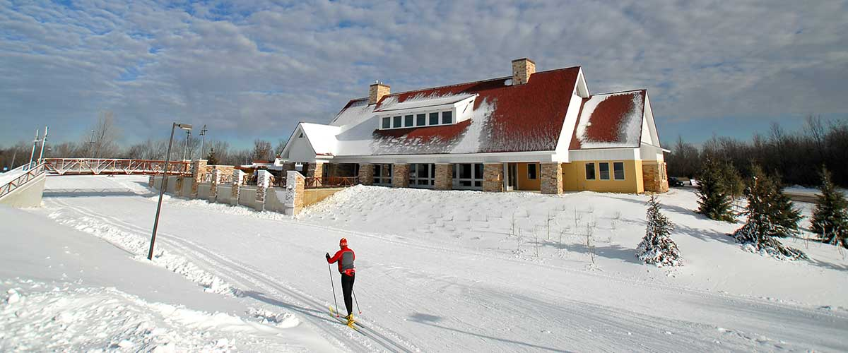 skiers glide past a large ski chalet