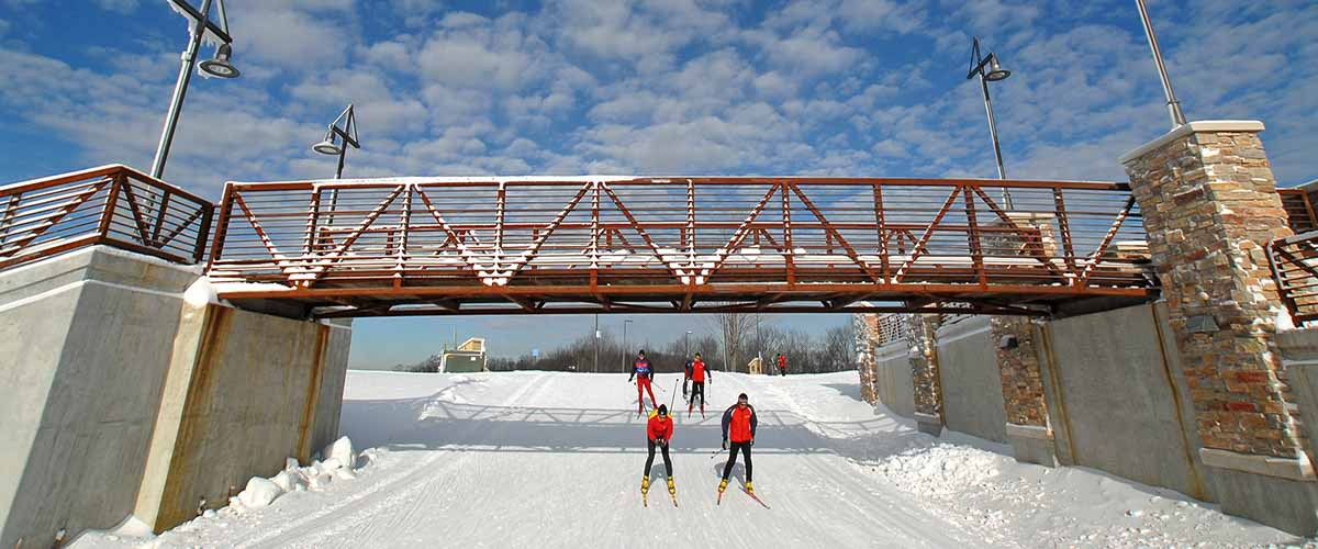 cross country skiers under a bridge