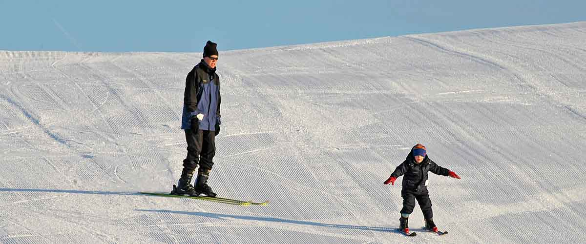 a father and son downhill skiing
