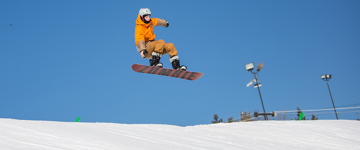 a snowboarder jumps over a hill