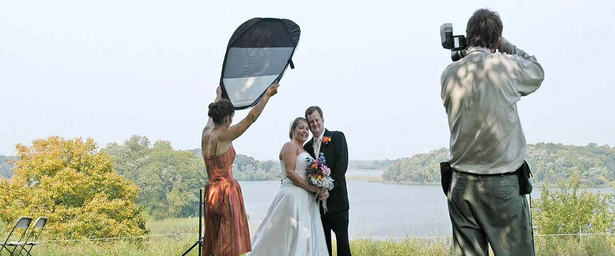 A photographer takes a picture of a bride and groom outside.