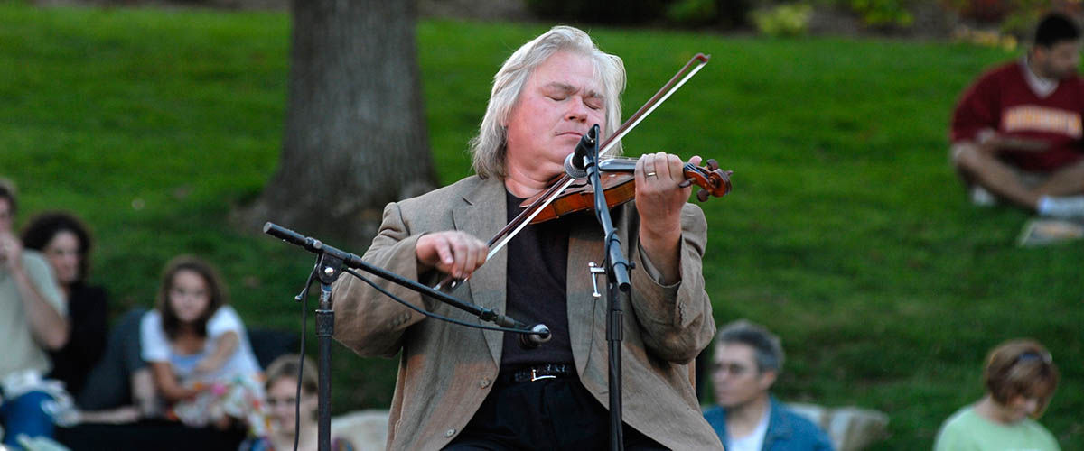 A man plays the violin at an outdoor concert