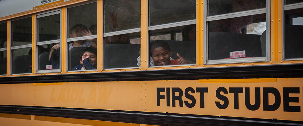 A boy looks out of a school bus window