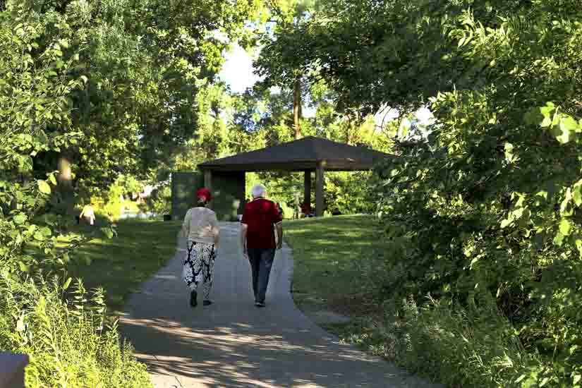 A couple walks along a shaded path