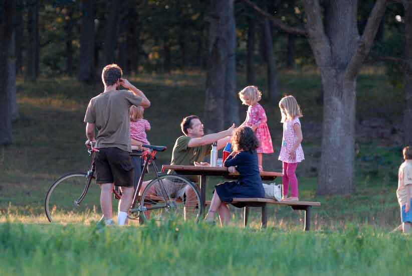 A family gathers around a picnic table