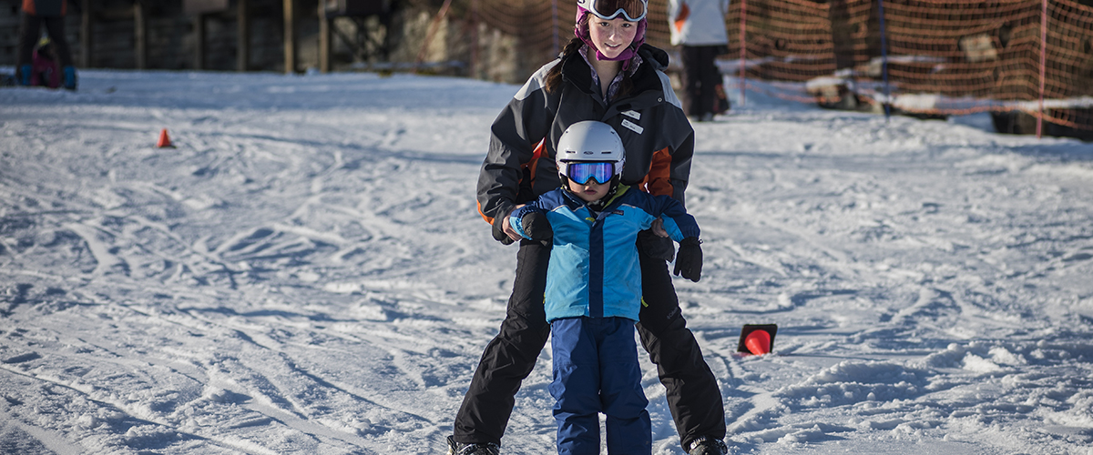 a ski instructor gives a young boy ski lessons