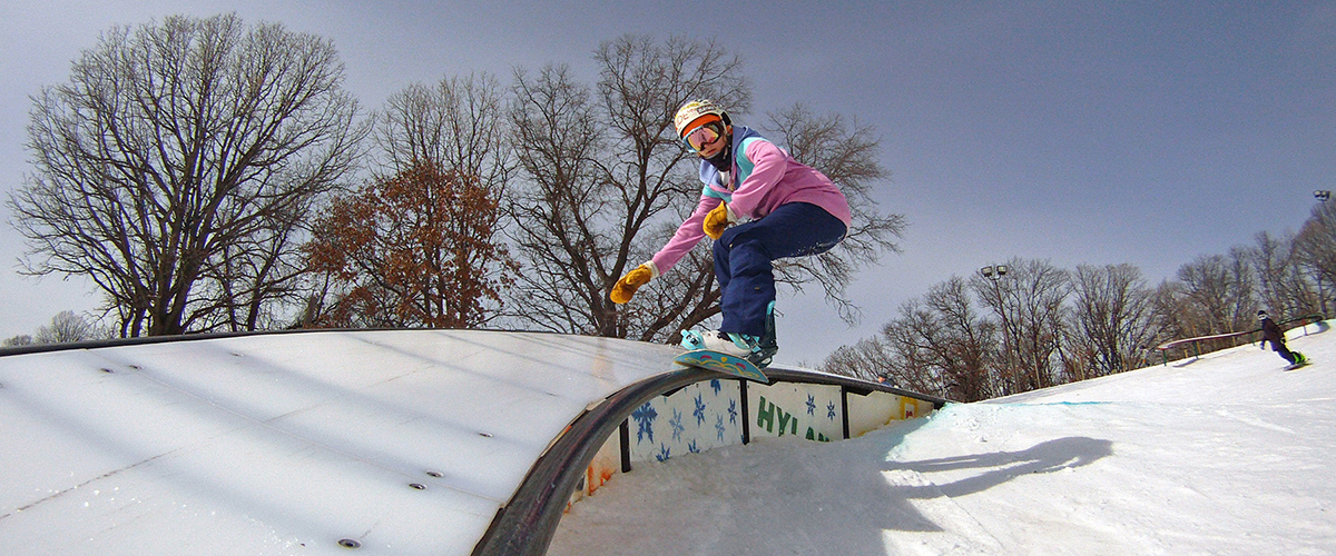 a girl snowboarder glides on a rail