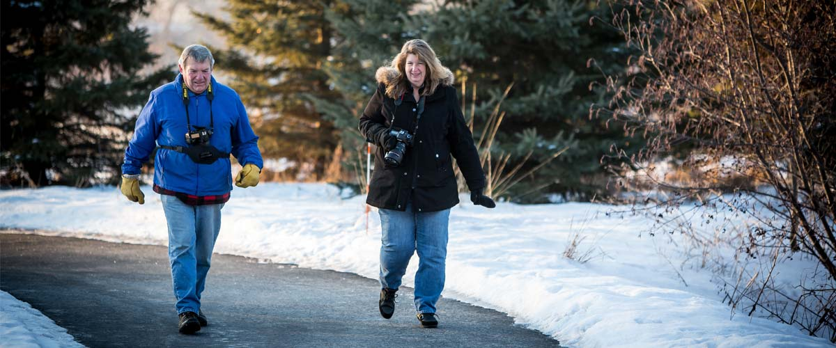 man and woman walking on paved path in winter