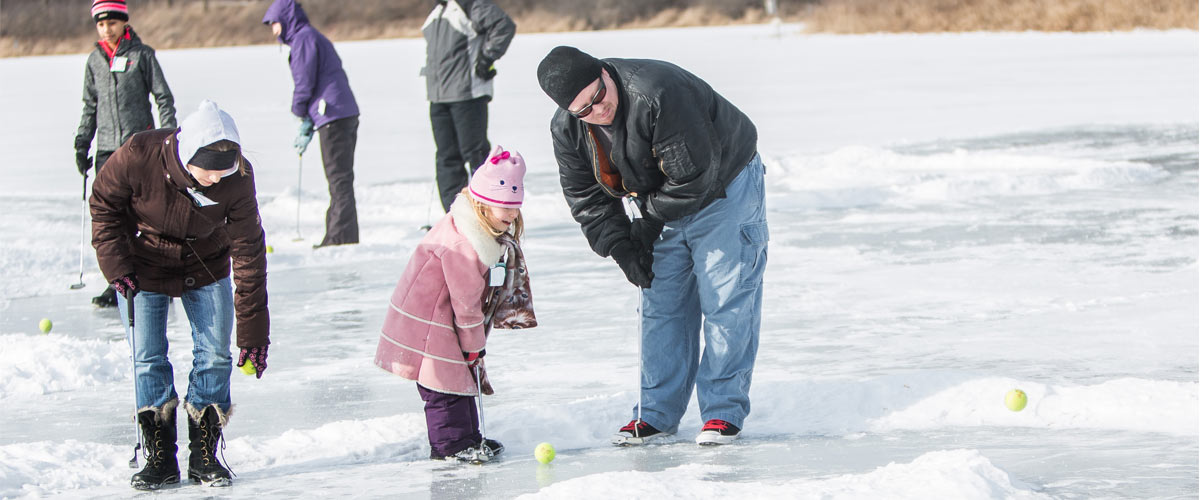family playing golf on a frozen lake