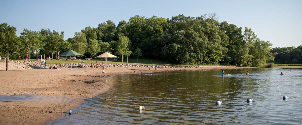 a beach with two umbrellas and trees in the background. a swimming area is roped off in the water and people are swimming.