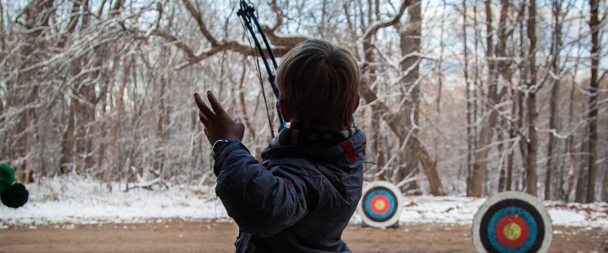 boy aiming a boy and arrow at targets with a background of trees and snow.