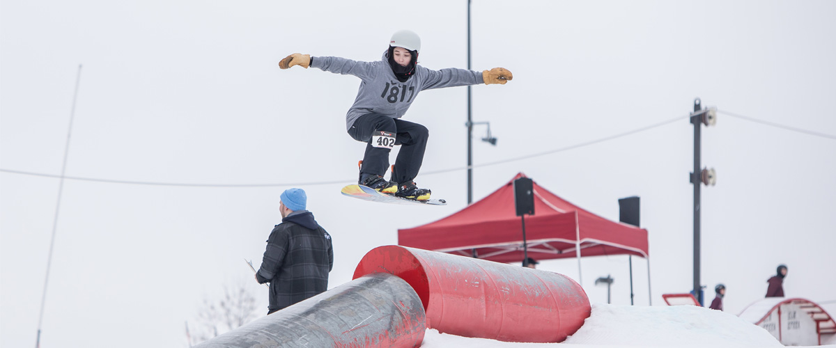 A snowboarder in mid-air over a pipe