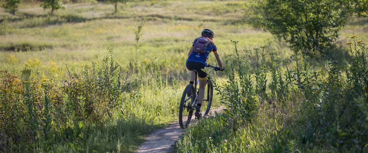 person riding a mountain bike through grassy area