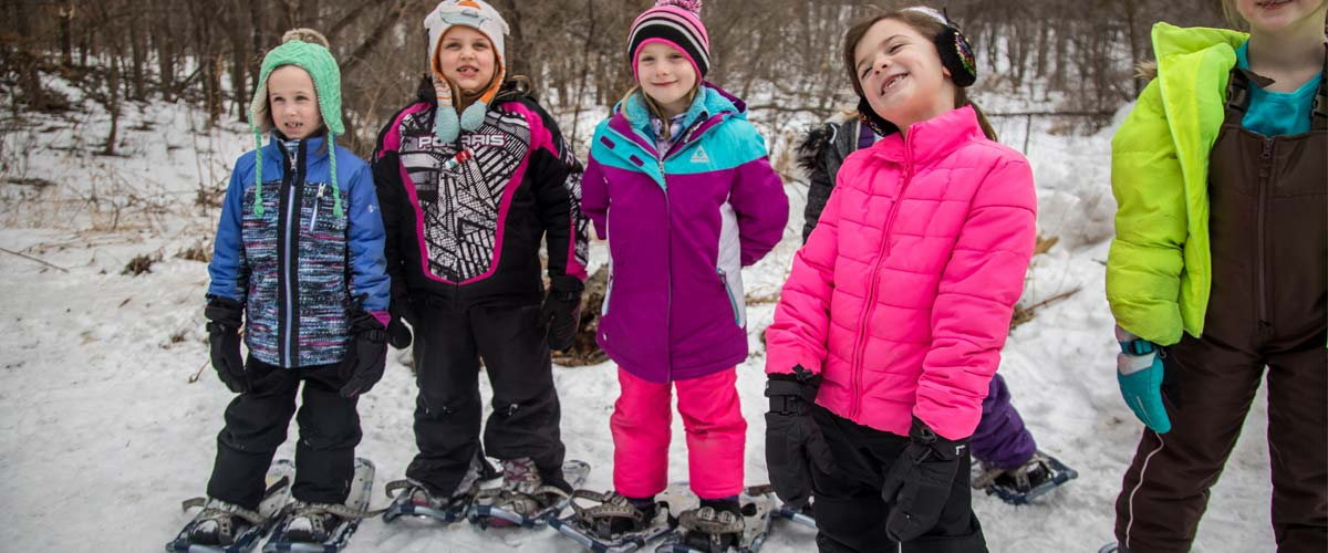 a group of young girls smiling and wearing snowshoes