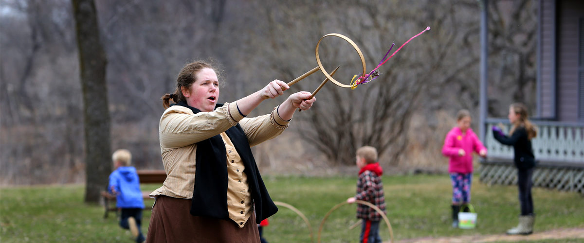 A woman in historic costume playing a traditional game with a wooden hoop