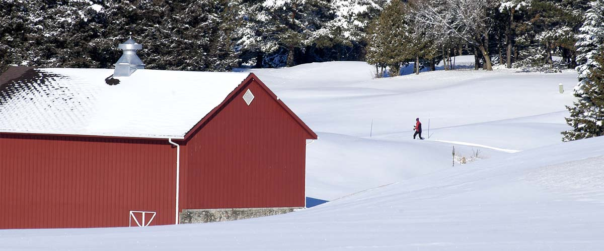 A cross-country skier skis by a red building in the snow.