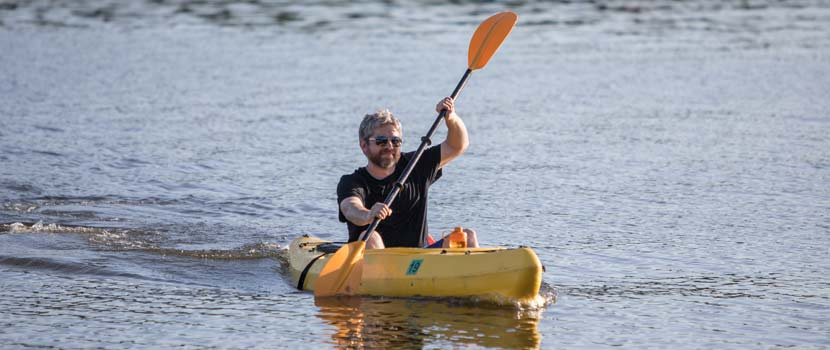a man paddling in a yellow kayak
