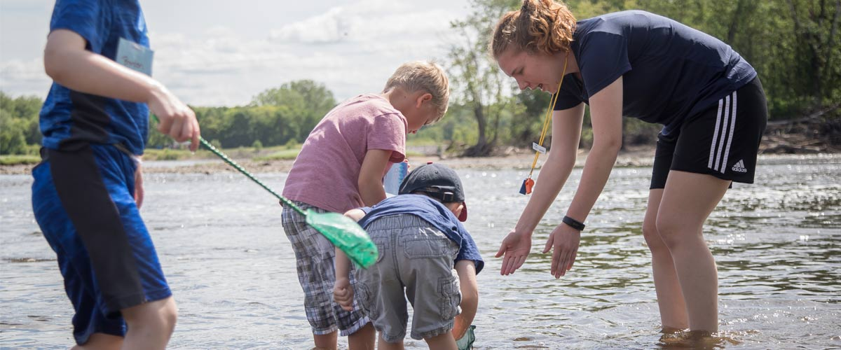 A teen girl helping kids dig in the water at summer camp