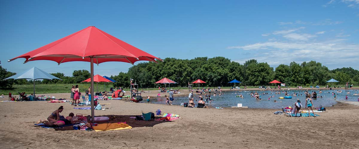 elm creek swim pond with a large red umbrella in the foreground