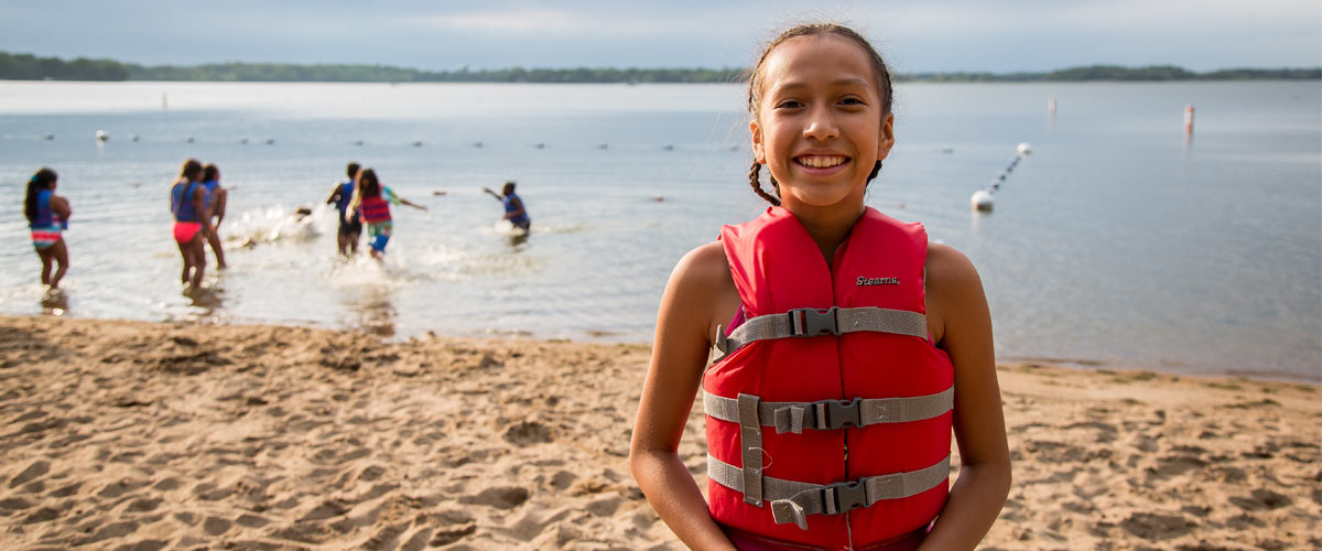 a girl in a life jacket smiling on the beach with kids playing in the water behind her.
