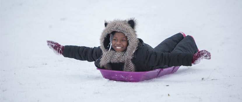 girl sledding on her stomach with her arms extended like an airplane