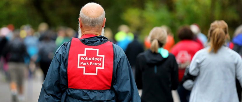 back of a volunteer wearing a red vest that says park patrol