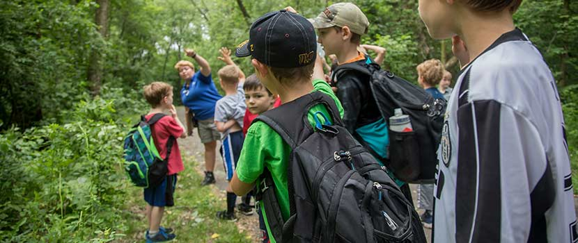 an instructor talking to a group of boys on a trail in the woods.