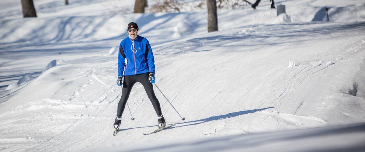 a man in a blue jacket and black pants cross-country skiing down a small hill.
